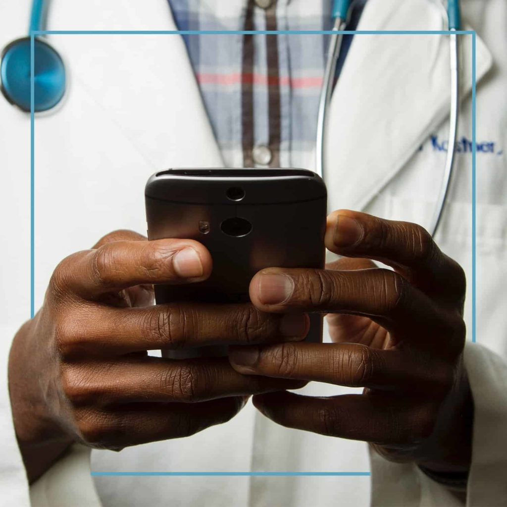 Doctor wearing a stethoscope looking at the screen on his phone